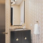 black vanity with brass handles in yellow powder room
