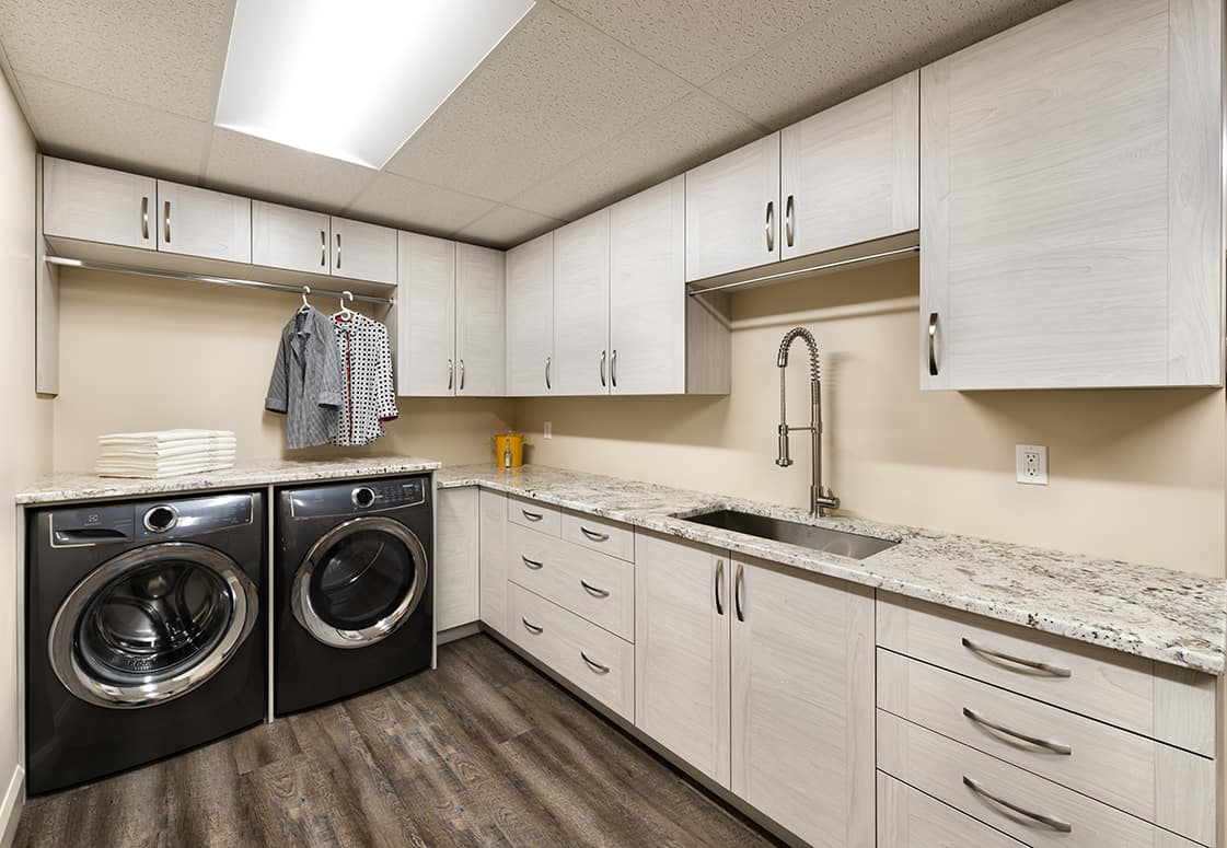 laundry room with grey cabinets and granite counters