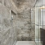 grey and brown tiled walk in shower with a niche