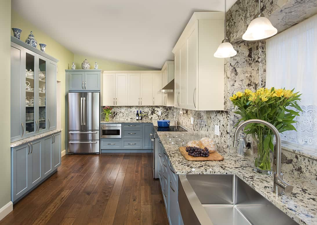kitchen with blue and cream cabinets and granite countertops and backsplash
