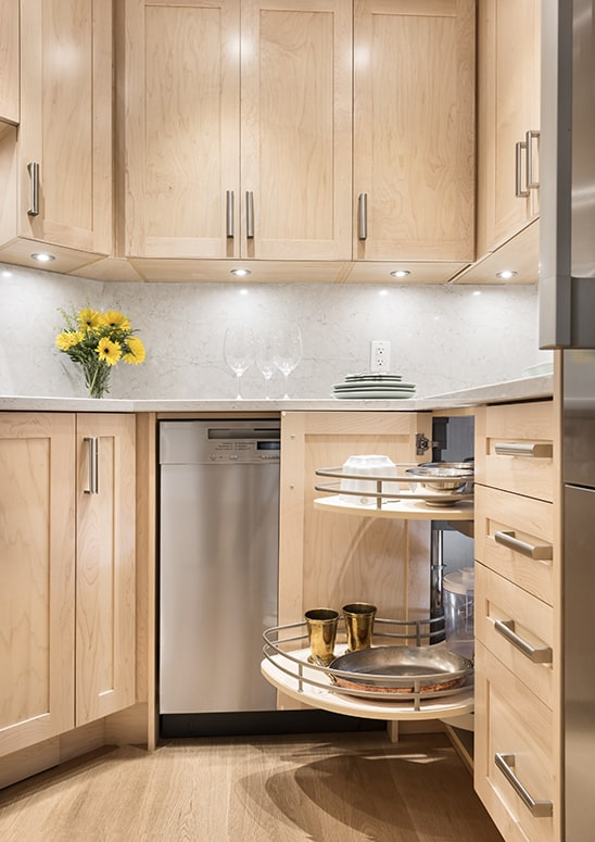 kitchen with pale wood cabinets and floors with lots of storage