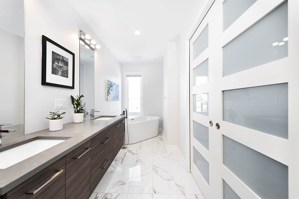 white bathroom with dark vanity and marble-effect tile
