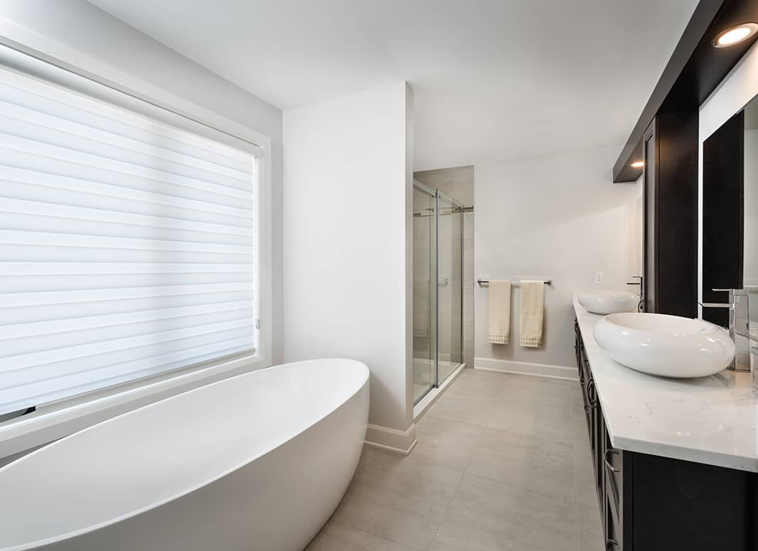 white bathroom with dark vanity with dual rounded vessel sinks